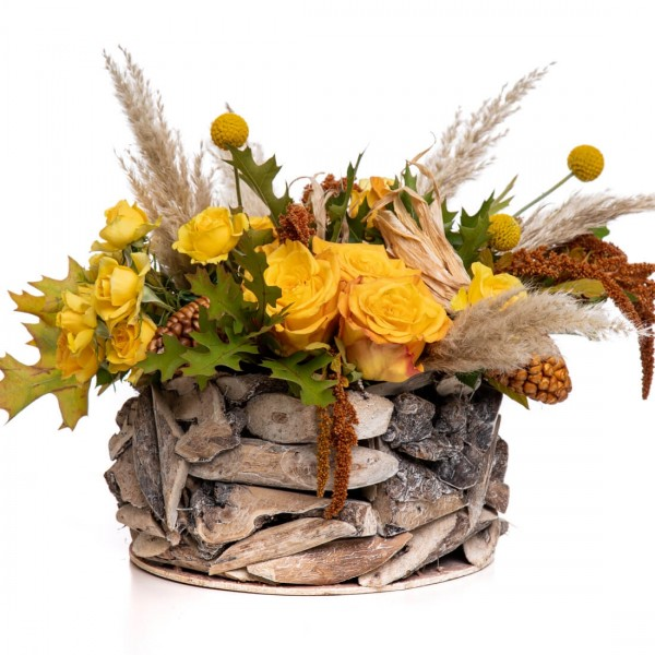 Floral arrangement in basket with craspedia and spray roses