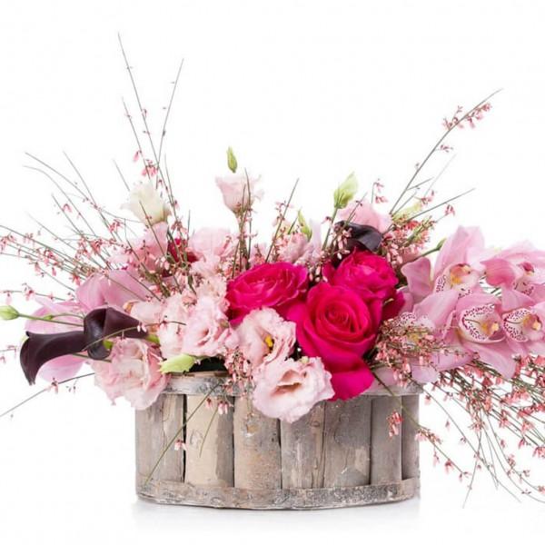 Floral arrangement in basket with cymbidium and genista