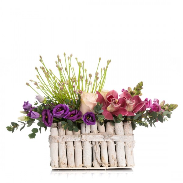 Floral arrangement in basket with roses and purple lisianthus