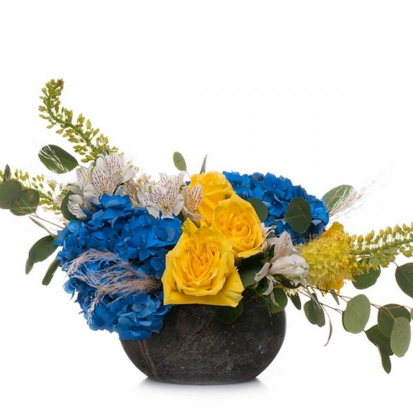 Floral arrangement with blue hydrangeas and yellow roses