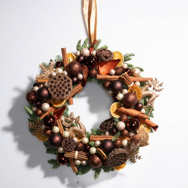 Christmas wreath made of natural fir with cinnamon, orange slices and balls