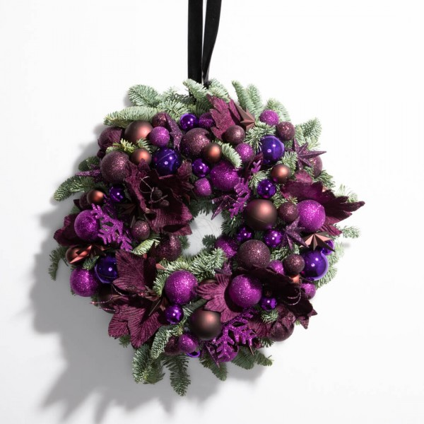 Christmas wreath made of natural fir and purple globes