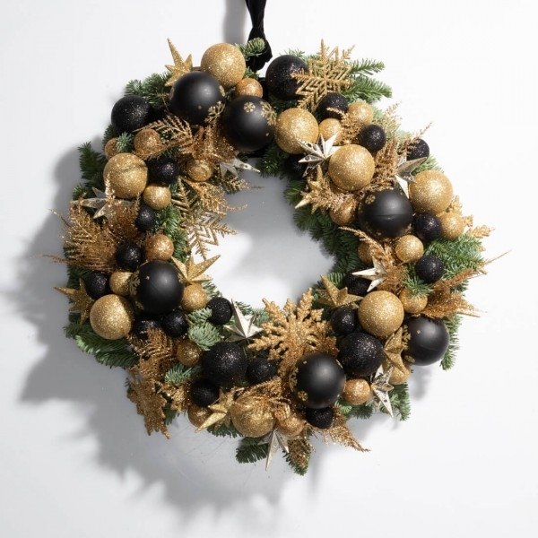 Christmas wreath made of natural fir with golden and black globes