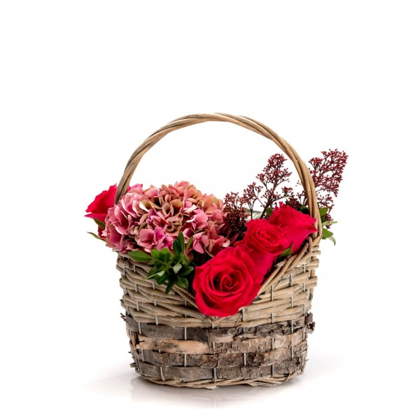 Floral arrangement in basket with roses and hydrangea