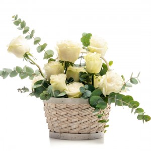 Floral arrangement in basket made of white roses, ruscus