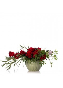 Floral arrangement in ceramic vase with red roses and skimmia