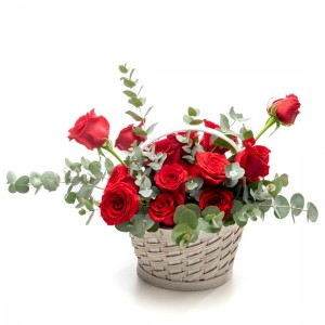 Floral arrangement in basket from red roses, ruscus